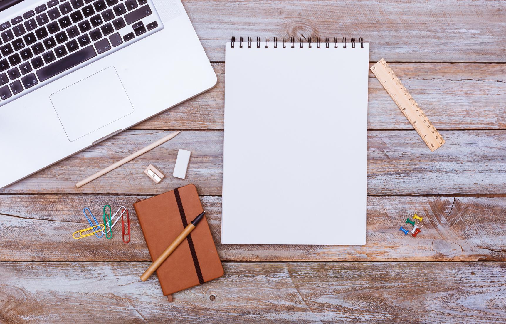 Symbolbild für SEO-Texten: Laptop, Block und Schreibmaterialien auf Holztisch von oben