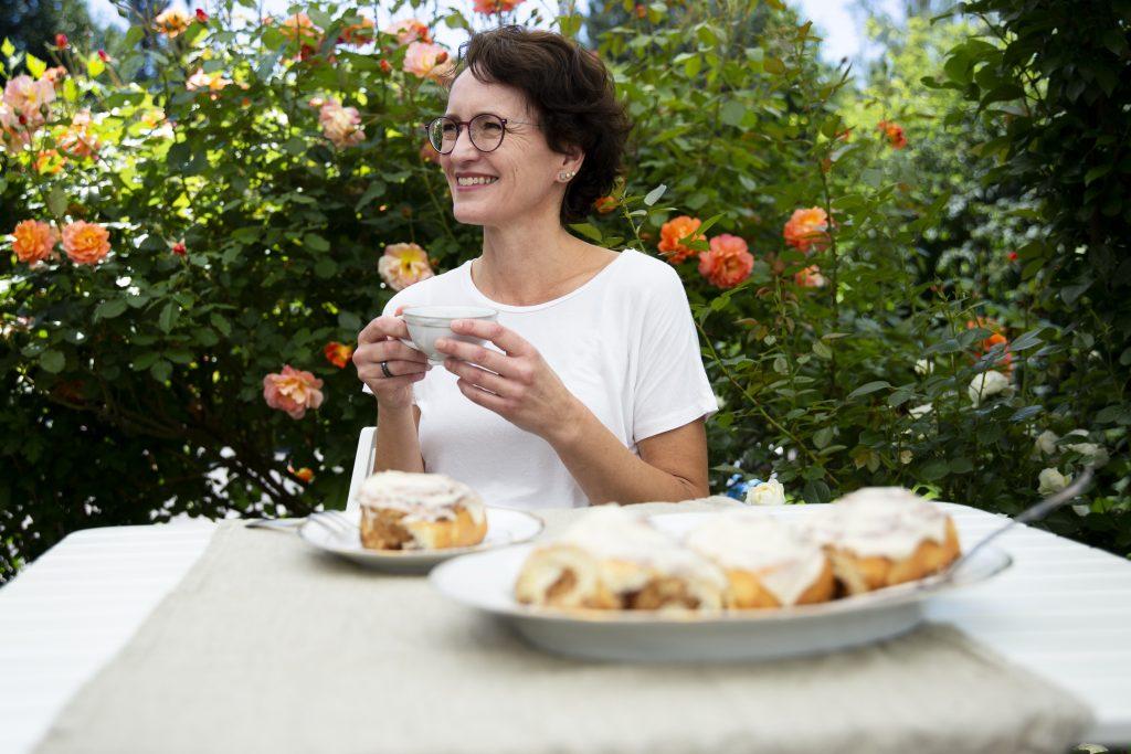 Eva Dragosits, mit Kaffee und Zimtschnecken auf der Terrasse